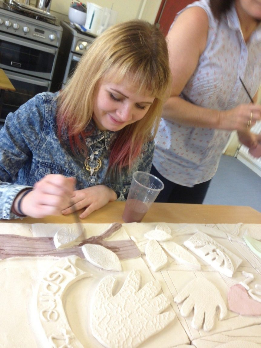 Hard at work, Natalie working on a clay tile mural